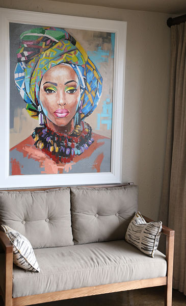Two seater couch in front of a painting of an African lady