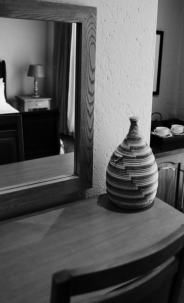 Black and white image of a vase on a desk